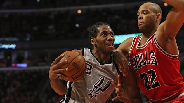 Kawhi Leonard of the San Antonio Spurs drives against Taj Gibson of the Chicago Bulls at the United Center (AFP)