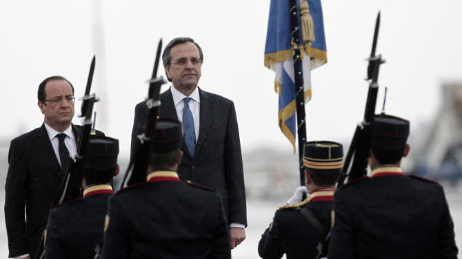 French President Francois Hollande, left, and Greek Prime Minister Antonis Samaras stand as they listen the French national anthem during a ceremony at the Eleftherios Venizelos airport, Athens, Tuesday. Feb. 19, 2013. Hollande is in Greece on a one day official visit. (AP Photo/Petros Giannakouris)