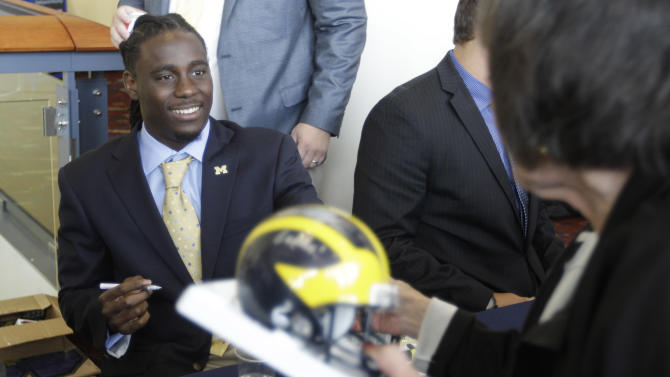 Michigan quarterback Denard Robinson signs autographs for fans as part of Big Ten Media Days and Kickoff Luncheon, Friday, July 27, 2012, in Chicago. (AP Photo/M. Spencer Green)