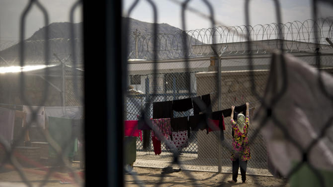 """Picture taken March 28, 2013 shows anAfghan female prisoner hanging up laundry on a small patch of open space surrounded by a high fence topped with razor at Badam Bagh, Afghanistan's central women's prison, in Kabul, Afghanistan. Twohundred-and-two women living in the six- year- old jail, the majority of the women are serving sentences of up to seven years for leaving their husbands, refusing to accept a marriage arranged by their parents, or choosing to leave their parent's home with a man of their choice, all so-called """"moral"""" crimes(. AP Photo/Anja Niedringhaus)"""