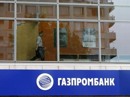 A person is pictured through a window above a Gazprombank branch in Moscow