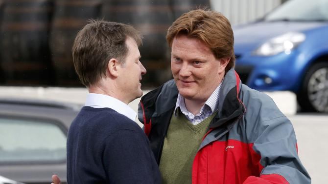 Nick Clegg, the leader of Britain's Liberal Democrat Party embraces party coleague Chief Secretary to the Treasury and local MP Danny Alexander after a visit to a whisky distillery in Inverness, Scotland