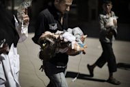 "A Syrian man carries his wounded daughter outside a hospital in the northern city of Aleppo on September 18, 2012. Amnesty accused Syrian forces Wednesday of waging ""relentless, indiscriminate"" attacks against its people as a Syrian army defector warned the regime would use chemical weapons as a last resort"