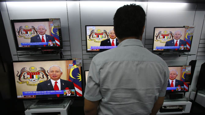 A customer watches a live broadcast of an announcement by Malaysian Prime Minister Najib Razak at an electrical shop in Klang, outside Kuala Lumpur, Malaysia, Wednesday, April 3, 2013. Najib dissolved Parliament to call for national elections expected later this month. (AP Photo/Lai Seng Sin)