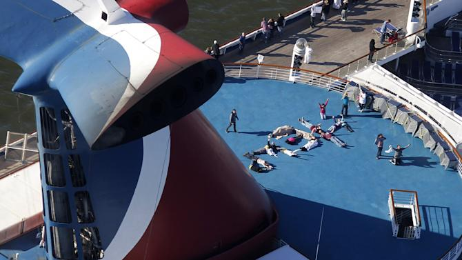 "FILE - In this Thursday, Feb. 14, 2013, file photo, passengers spell out the word ""HELP"" aboard the disabled Carnival Lines cruise ship Triumph as it is towed to harbor off Mobile Bay, Ala. Carnival Cruise Lines knew about the risk of leaks from engine fuel hoses and recommended taking precautions on the ill-fated Carnival Triumph, which caught on fire at sea, according to documents filed in recent days. A ""compliance notice report"" sent to the Triumph one month before it departed Galveston on Feb. 7 for what was planned as a four-day cruise recommended spray shields be installed on engines' flexible fuel hoses, according to documents filed Tuesday, Dec. 17, 2013, by Carnival Cruise Lines in federal court in Miami. (AP Photo/Gerald Herbert, File)"
