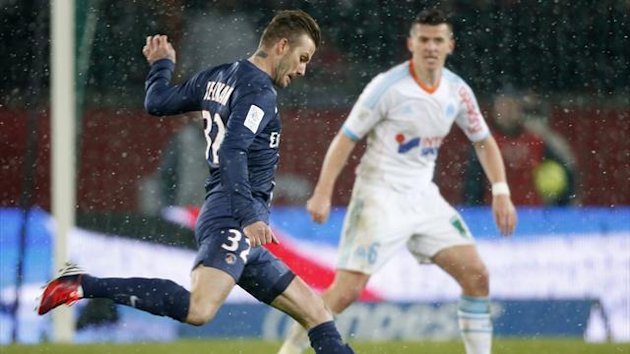 Paris Saint-Germain's David Beckham (L) challenges Olympic Marseille's Joseph Barton during their French Ligue 1