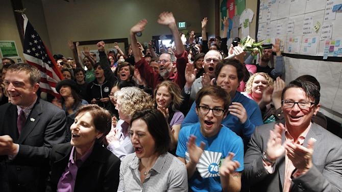 Supporters of Referendum 74, which would uphold the state's new same-sex marriage law, cheer at a news conference Wednesday, Nov. 7, 2012, in Seattle. Supporters of gay marriage in Washington state declared victory Wednesday, saying they don't see a way for their opponents to prevail as votes continue to trickle in on Referendum 74. R-74 asked Washingtonians to approve or reject a state law legalizing same-sex marriage that lawmakers passed earlier this year. That law was signed by Gov. Chris Gregoire but has been on hold pending the election's outcome. With about half of the expected ballots counted Tuesday night, R-74 was passing with 52 percent of the vote. (AP Photo/Elaine Thompson)