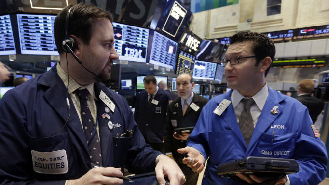 Traders Mike Mozian, left, and Leon Montana confer on the floor of the New York Stock Exchange Wednesday, Jan. 30, 2013.  Stocks are falling after the government revealed that economic growth shrank in the final quarter of 2012. (AP Photo/Richard Drew)