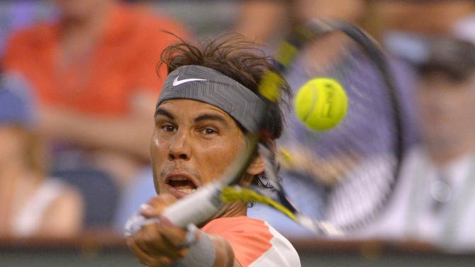 Rafael Nadal, of Spain, returns a shot to Alexandr Dolgopolov, of Ukraine, during their match at the BNP Paribas Open tennis tournament, Monday, March 10, 2014, in Indian Wells, Calif. Dolgopolov won 6-3, 3-6, 7-6 (5). (AP Photo/Mark J. Terrill)
