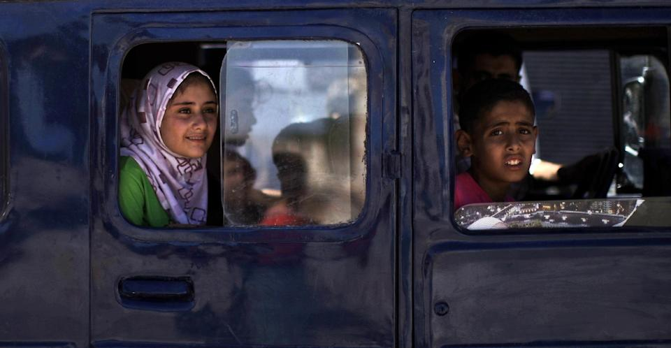 Syrian children look out from the windows of a vehicle in the city of Azaz, on the outskirts of Aleppo, Syria, Wednesday, Aug. 22, 2012. (AP Photo/Muhammed Muheisen)