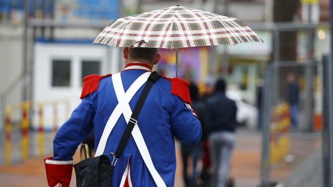 Carnival reveller uses umbrella after Rosenmontag parade cancelled in Mainz
