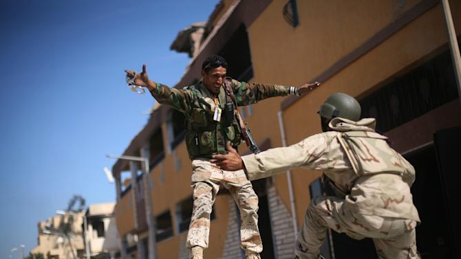 Revolutionary fighters celebrate the capture of Sirte, Libya, Thursday, Oct. 20, 2011. Officials in Libya's transitional government said Moammar Gadhafi was captured and possibly killed Thursday when revolutionary forces overwhelmed his hometown, Sirte, the last major bastion of resistance two months after the regime fell. (AP Photo/Manu Brabo)