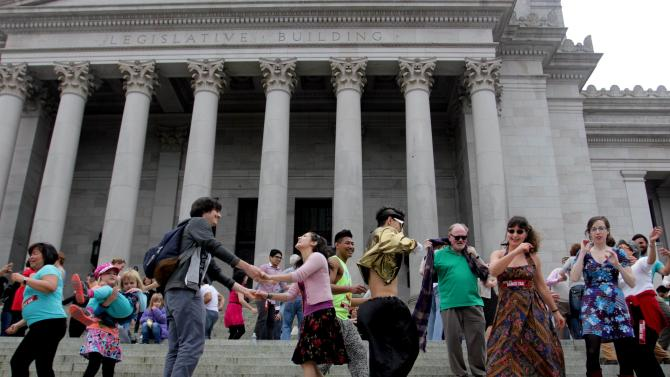 People dance on the steps of the Capitol in Olympia, Wash., Monday, April 1, 2013 to protest a decades-old state tax on dance venues. Washington state has had the tax, which targets venues that provide an opportunity to dance, since the 1960s. A measure to repeal it has cleared a committee and is awaiting a floor vote in the Senate. (AP Photo/Manuel Valdes)