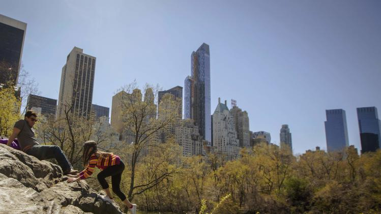 A young girl climbs on the rocks as her father enjoys the view of the Manhattan skyline from Central Park in New York