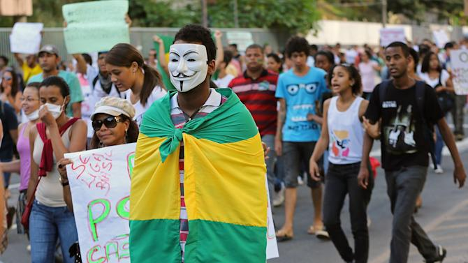 A masked demonstrator carries a Brazilian flag on his back near the Arena Fonte Nova stadium in Salvador, Brazil, Saturday, June 22, 2013. Demonstrators once again took to the streets of Brazil on Saturday, continuing a wave of protests that have shaken the nation and pushed the government to promise a crackdown on corruption and greater spending on social services. (AP Photo/Andre Penner)
