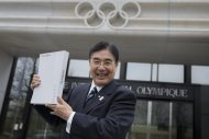 Masato Mizuno, Chief Executive Officer for the Tokyo 2020 Olympic bid, pose for photographer in front of the IOC headquarter before they submit candidature bid for 2020 Tokyo Olympic summer games at the International Olympic Committee, IOC, headquarters in Lausanne, Switzerland, Monday, Jan. 7, 2013. The International Olympic Committee announced that Istanbul, Tokyo and Madrid have made it on to the short list of cities bidding to host the 2020 Olympic Games. (AP Photo/Keystone, Jean-Christophe Bott)