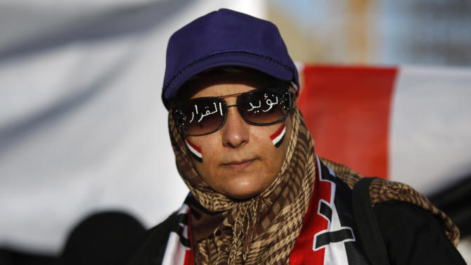 """A female protestor with Yemen's flag painted on her face and Arabic writing on sunglasses that reads, """"we support the decision,"""" during a rally to show support for President Abed Rabbu Mansour Hadi, in Sanaa, Yemen, Thursday, Dec. 20, 2012. (AP Photo/Hani Mohammed)"""
