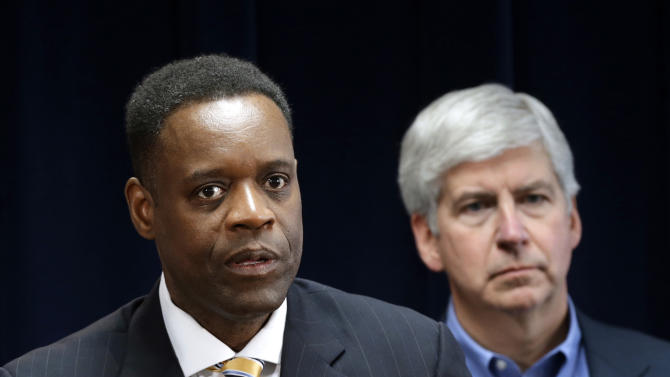 FILE - In this March 14, 2013 file photo, Washington-based attorney Kevyn Orr, left, speaks at a news conference in Detroit as Michigan  Gov. Rick Snyder listens. Orr starts work Monday, March 25, 2013, as Detroit's emergency manager and the turnaround expert says his first tasks will be reviewing the city's financial data and listening. (AP Photo/Paul Sancya, File)