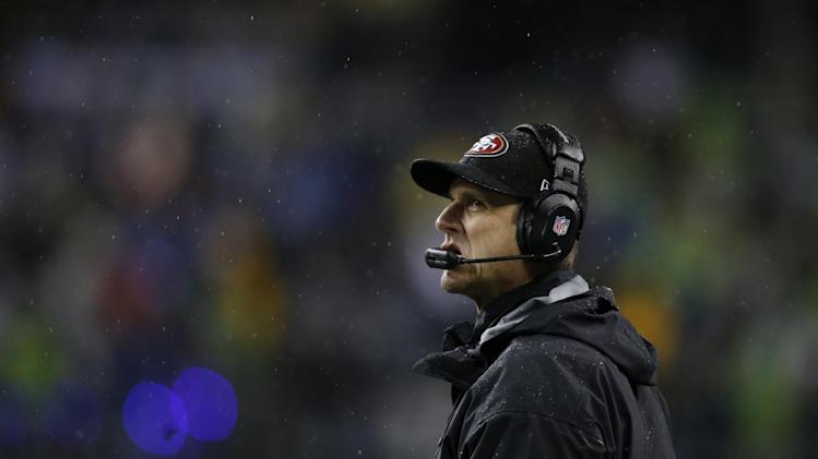 San Francisco 49ers' head coach Jim Harbaugh looks to the scoreboard in the first half of an NFL football game against the Seattle Seahawks, Sunday, Dec. 23, 2012, in Seattle. (AP Photo/John Froschauer)