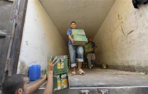Workers transfer boxes of juice from a truck at a food market in Benghazi
