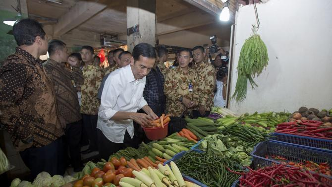 Indonesian President Joko Widodo purchases carrots during a visit to a market in Jakarta