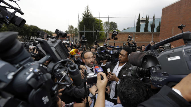"""Agustin Acosta, center left, lawyer of the imprisoned Frenchwoman Florence Cassez, speaks to reporters outside the prison where she had been held in Mexico City, Wednesday, Jan. 23, 2013. A Mexican Supreme Court panel voted Wednesday to release Cassez, a Frenchwoman who says she was unjustly sentenced to 60 years in prison for kidnapping and whose case became a cause celebre in France, straining relations between the two countries. A police convoy with sirens flashing escorted a white sports utility vehicle out of the prison where Cassez had been held later Wednesday, presumably carrying her to the Mexico City airport. Relatives of kidnap victims angrily shouted """"Killer!"""" as the vehicle pulled away. (AP Photo/Andres Leighton)"""