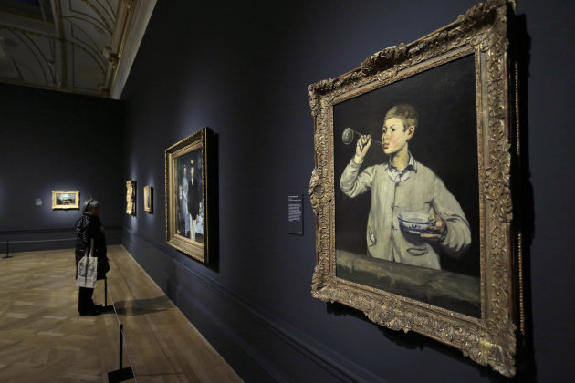 People look at Manet paintings during a press viewing of 'Manet: Portraying Life', a major exhibition at the Royal Academy of Arts in central London, Tuesday, Jan. 22, 2013. The exhibition that will r