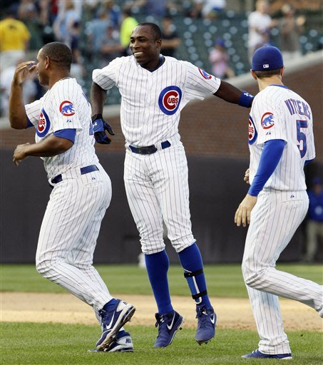 Chicago Cubs' Alfonso Soriano, center, celebrates with teammates Carlos Marmol, left, and Josh Vitters, right, after hitting a game-winning RBI-single during the ninth inning of a baseball game against the Milwaukee Brewers in Chicago, Thursday, Aug. 30, 2012. The Cubs won 12-11.