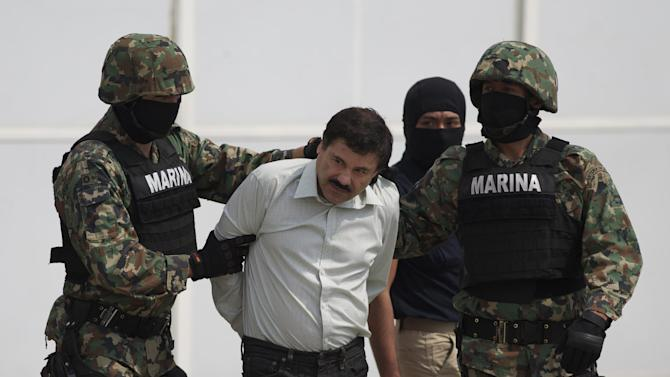 """Joaquin """"El Chapo"""" Guzman is escorted to a helicopter in handcuffs by Mexican navy marines at a navy hanger in Mexico City, Mexico, Saturday, Feb. 22, 2014. A senior U.S. law enforcement official said Saturday, that Guzman, the head of Mexicoís Sinaloa Cartel, was captured alive overnight in the beach resort town of Mazatlan. Guzman faces multiple federal drug trafficking indictments in the U.S. and is on the Drug Enforcement Administrationís most-wanted list. (AP Photo/Eduardo Verdugo)"""