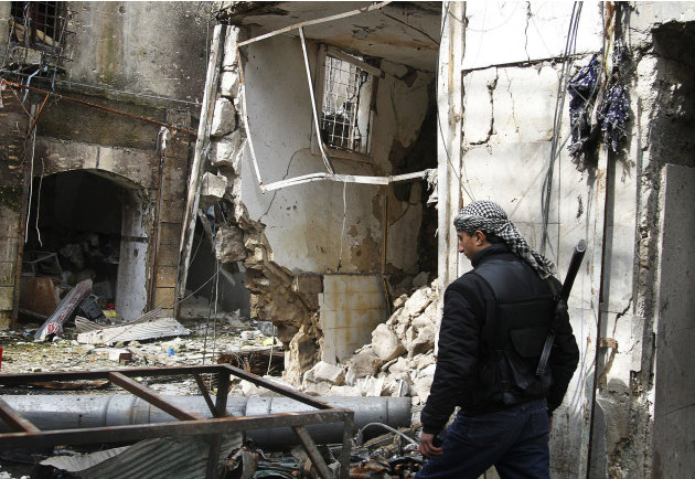 In this Friday February 8, 2013 photo, a Free Syrian Army fighter walks past destroyed shops in Aleppo, Syria. Syrian rebels brought their fight within a mile of the heart of Damascus on Friday, seizi