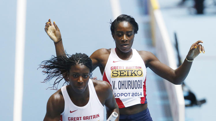 Britain's Victoria Ohuruogu, right, hands over the baton to Christine Ohuruogu in the women's 4x400m relay heat during the Athletics World Indoor Championships in Sopot, Poland, Saturday, March 8, 2014. (AP Photo/Petr David Josek)