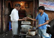 Ram Singh (R) passes a glass of tea to a customer at a shop in old quarters of New Delhi. Singh, 17, earns just one dollar from the 100 cups of tea he makes every day outside Delhi railway station, but each evening, after packing up, he goes to the bank and deposits nearly half of it