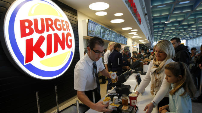 Customers buy a meal at a Burger King restaurant in Marseille-Provence airport, in Marignane, France, Saturday, Dec. 22, 2012. Fifteen years after leaving France, the U.S. hamburger chain Burger King returned with the opening of a restaurant in Marseille-Provence airport. (AP Photo/Claude Paris)
