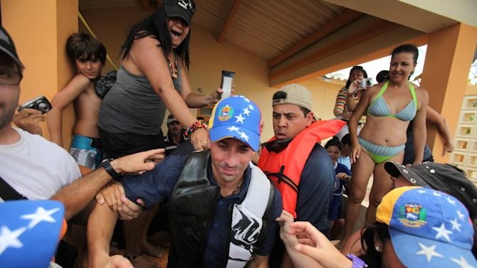 Opposition presidential candidate Henrique Capriles greets supporters during a campaign visit at Morrocoy Keys near Chichiriviche, Venezuela, Good Friday, March 29, 2013. Holy Week in Venezuela is a time when millions traditionally take a welcome pause from work and politics to go on vacation. Yet that hasn't stopped Venezuela's time-pressed presidential candidates from sprinting through the holidays toward an April 14 election to replace the late Hugo Chavez, as they try to define both themselves and each other within weeks. Capriles will run against Chavez's chosen successor, acting President Nicolas Maduro.(AP Photo/Fernando Llano)