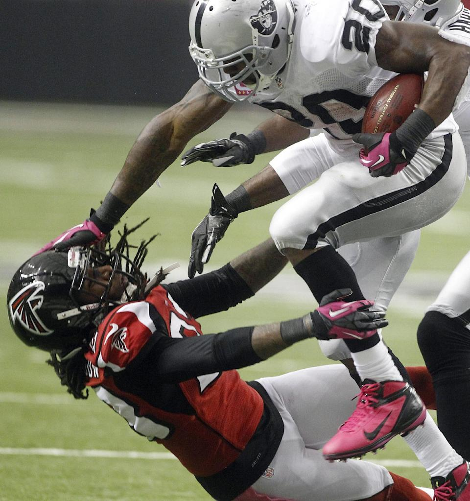 Oakland Raiders Darren McFadden (20) stiff-arms Atlanta Falcons cornerback Dunta Robinson (23) to the ground during the second half of an NFL football game, Sunday, Oct. 14, 2012, in Atlanta. (AP Photo/John Bazemore)