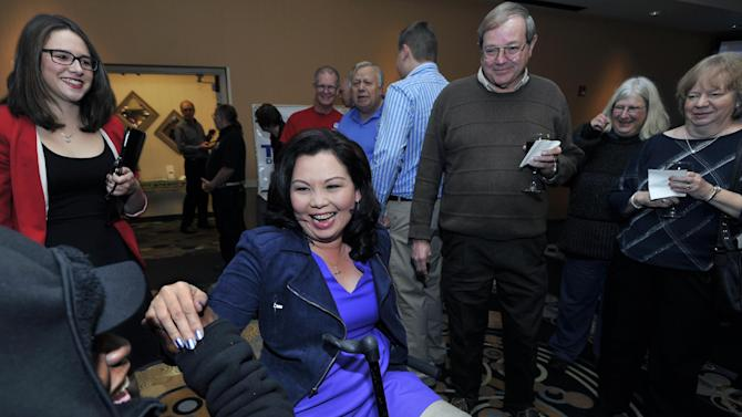 Tammy Duckworth, the Democratic nominee for the Illinois' 8th congressional district of the United States House of Representatives greets fellow veteran Octavia Mitchell in Elk Grove Village, Ill., Tuesday, Nov. 6, 2012. Duckworth, an Iraq War Veteran, served as a U.S. Army helicopter pilot and suffered severe combat wounds, losing both of her legs. (AP Photo/Paul Beaty)