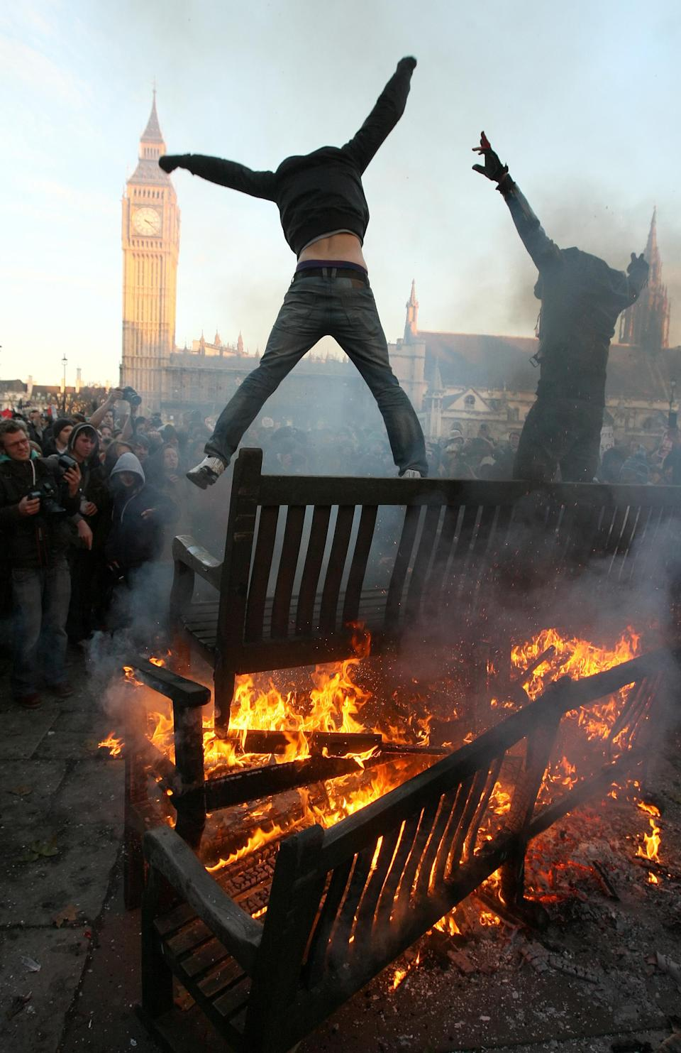 Two demonstrators jump from the top of a bonfire in Parliament Square, as students demonstrate in Westminster, London, against planned tuition fee increases Thursday Dec. 9, 2010. (AP Photo/Dominic Lipinski/PA)  UNITED KINGDOM OUT
