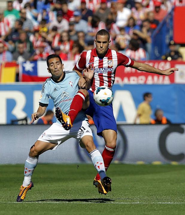 Atletico de Madrid's Mario Suarez, right, in action with Celta de Vigo's Charles from Brazil, left, during a Spanish La Liga soccer match at the Vicente Calderon stadium in Madrid, Spain, Sunday, Oct.