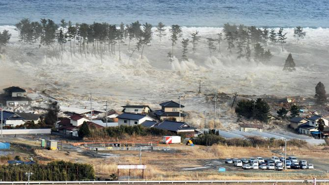FILE -In this March 11, 2011 file photo, waves of a tsunami hit residences after a powerful earthquake in Natori, Miyagi prefecture (state), Japan.  A government-commissioned panel of experts said Saturday March 31, 2012 a tsunami unleashed by a magnitude-9.0 earthquake in the Nankai trough, which runs east of Japan's main island of Honshu to the southern island of Kyushu, could top 34 meters. The revisions, posted on a government website, are based on new research following last March's magnitude-9.0 earthquake and tsunami. (AP Photo/Kyodo News, File) MANDATORY CREDIT, NO LICENSING ALLOWED IN CHINA, HONG KONG, JAPAN, SOUTH KOREA AND FRANCE