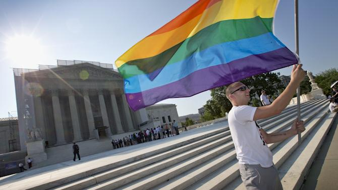 Vin Testa of Washington waves a rainbow flag in support of gay rights outside the Supreme Court in Washington, Tuesday, June 25, 2013, as key decisions are expected to be announced. The Supreme Court resolved five cases, including affirmative action, on Monday. That leaves disputes about gay marriage and voting rights among the six remaining cases. The justices are meeting again Tuesday to issue some opinions and will convene at least one more time. (AP Photo/J. Scott Applewhite)