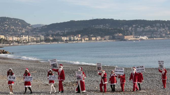 Anti-fur activists from the Coalition to Abolish the Fur Trade (CAFT) who are dressed in Santa costumes demonstrate on a beach in Nice