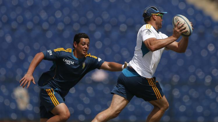South Africa's Kallis runs with a rugby ball as teammate de Kock chases him during a practice session ahead of their final One Day International cricket match against Sri Lanka in Hambantota