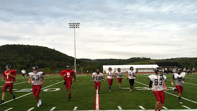 In this Sept. 9, 2013 photo, the Mansfield University sprint football practices in Mansfield, Pa. Mansfield, which played the first night football game in 1892, is scheduled to play its first home game under the lights in more than 120 years on Saturday, Sept. 14. (AP Photo/Michael Rubinkam)