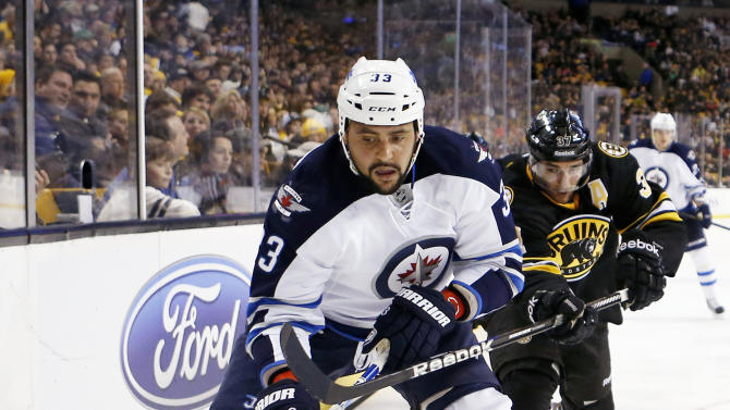 Winnipeg Jets' Dustin Byfuglien (33) and Boston Bruins' Patrice Bergeron (37) battle for the puck during the second period of an NHL hockey game in Boston, Monday, Jan. 21, 2013. (AP Photo/Michael Dwyer)