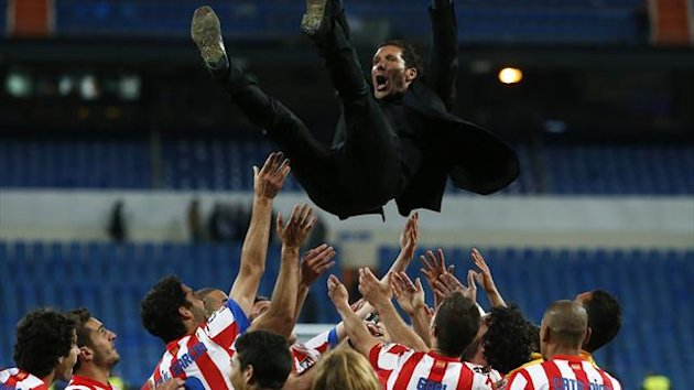Atletico Madrid's coach Diego Simeone is thrown in the air by his players (Reuters)
