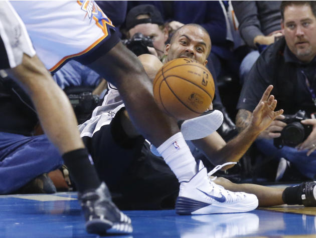 San Antonio Spurs guard Tony Parker (9) passes off after falling down in the second quarter of an NBA basketball game against the Oklahoma City Thunder in Oklahoma City, Wednesday, Nov. 27, 2013