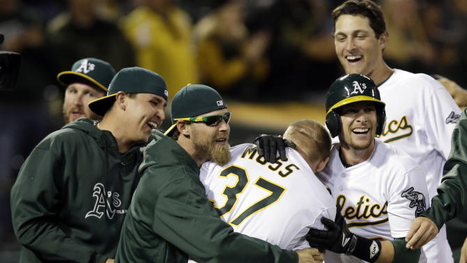 Oakland Athletics' Brandon Moss (37) is mobbed by teammates after his game-winning two-run home run against the Los Angeles Angels during a baseball game on Tuesday, April 30, 2013 in Oakland. Calif. Oakland won 10-8 in 19 innings. (AP Photo/Marcio Jose Sanchez)