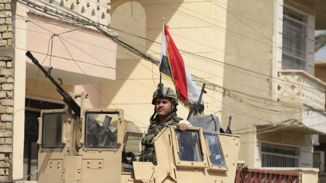 An Iraqi soldier surveys the scene from the top of an armored vehicle in Baghdad's Adhamiya district, Iraq, Thursday, April 18, 2013. The Iraqi government has tightened its security measures as the country prepares to provincial elections. (AP Photo/ Karim Kadim)