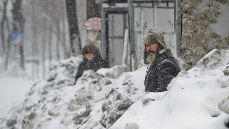People wait in a snowed in bus stop during a blizzard in Bucharest, Romania, Wednesday, Jan. 29, 2014. Weather forecasters issued a code red severe weather warning as a second wave of blizzards affects the southeastern regions of Romania disrupting road and rail traffic.(AP Photo/Vadim Ghirda)