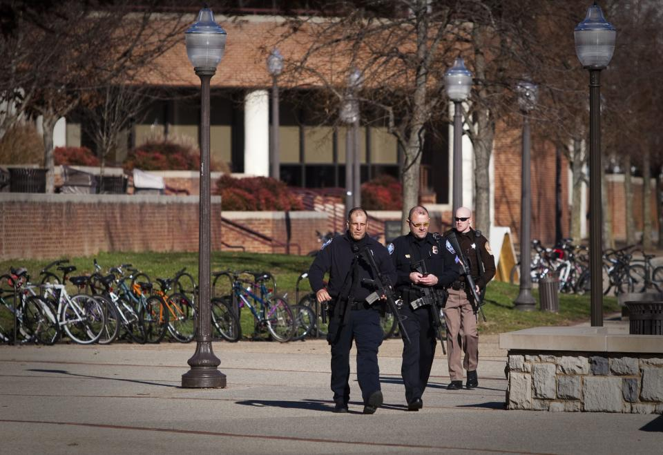 Police continue their investigation on the campus of of Virginia Tech in Blacksburg, Va. after a gunman killed a police officer in a school parking lot Thursday and was found dead nearby Thursday, Dec. 8, 2011. (AP Photo/The Roanoke Times, Sam Dean)